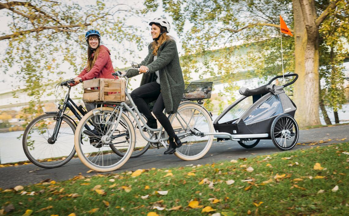 Frauen radeln mit Kinder-Fahrradanhänger im Herbst