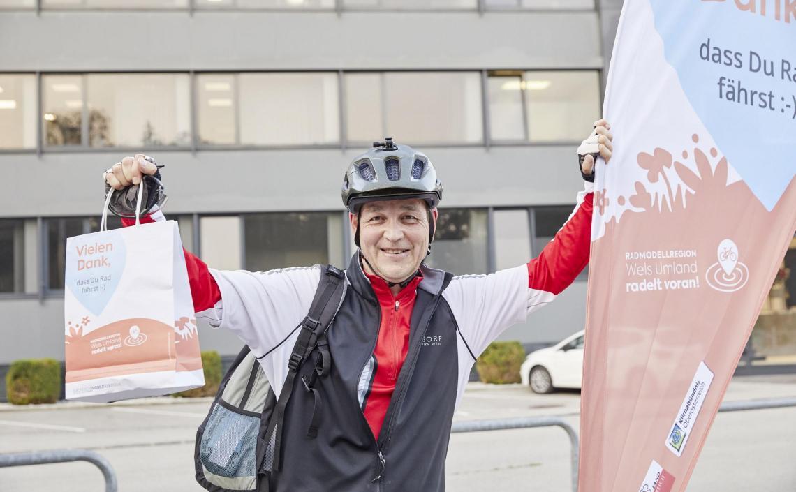 Mann auf Fahrrad und mit Früstückssackerl