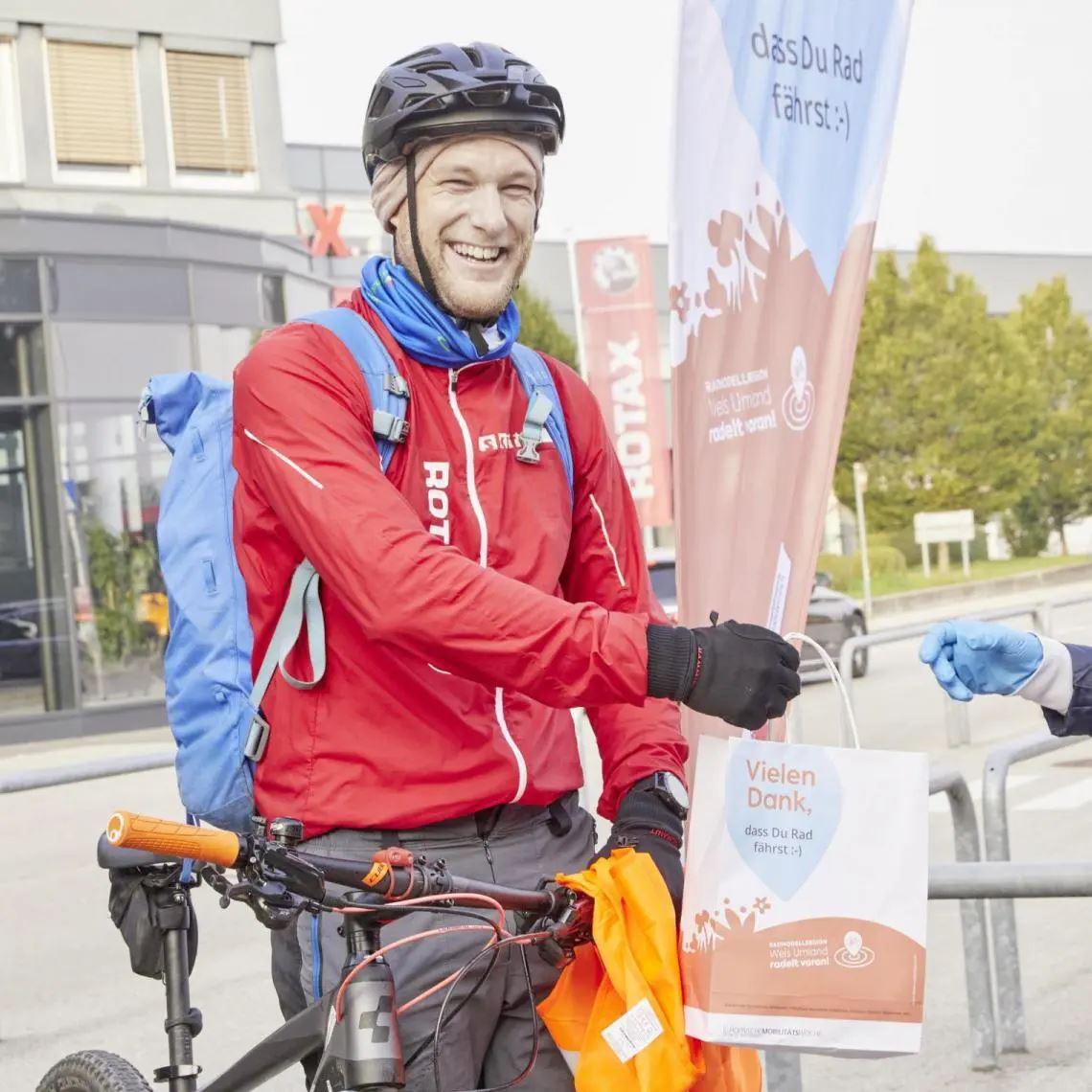 Mann auf Fahrrad mit Früstückssackerl