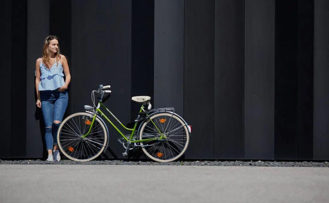 Frau steht neben Fahrrad