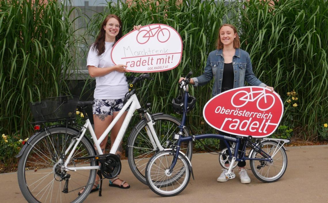 Frauen mit Fahrrädern und Oberösterreich radelt Schildern
