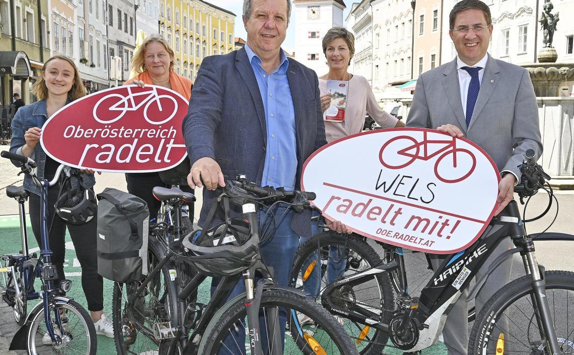 Personen mit Fahrrädern und Oberösterreich radelt Schildern