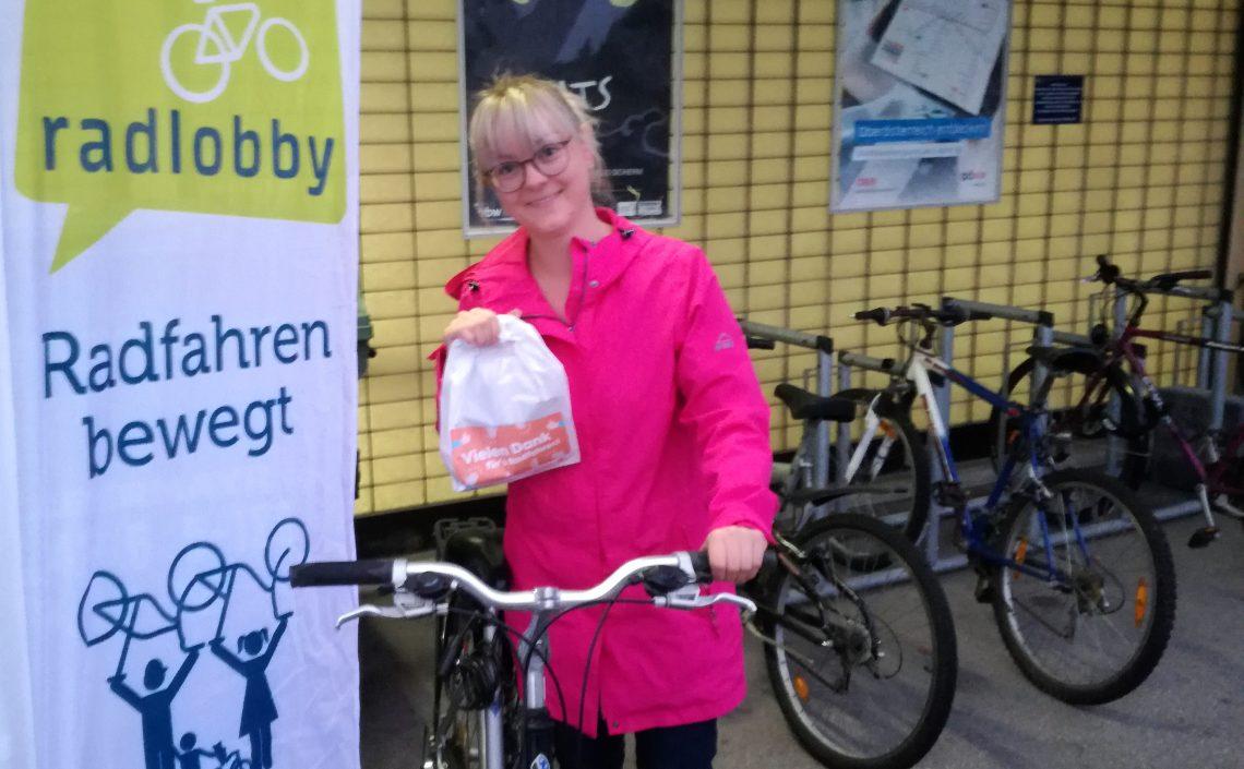 Frau mit Fahrrad und Frühstückssackerl
